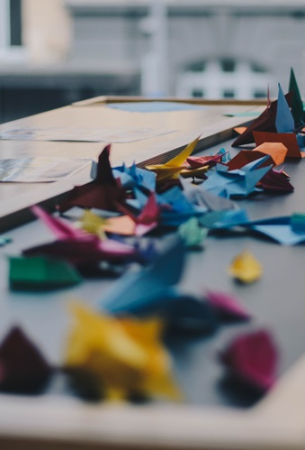 A table top with many origami paper cranes in different stages of progress